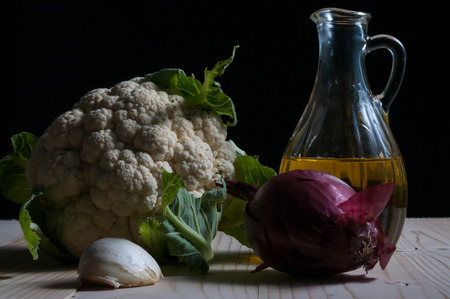 Low key still life with lettuce, onion, garlic and olive oil