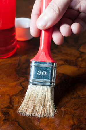Applying oil and wax wood finish with a brush Stock Photo
