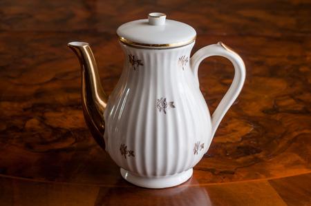 A ceramic teapot on a mahogany table