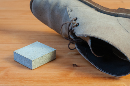 A suede eraser and a paire of suede boots on a wooden table Imagens - 92110295