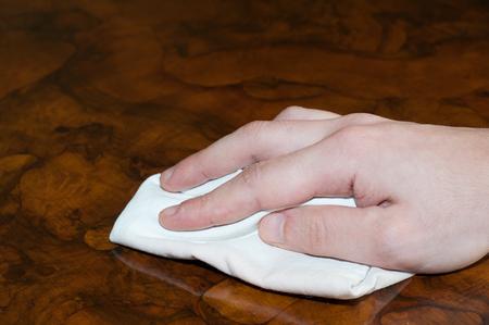 천으로 오래 된 나무 테이블을 청소하는 손. 가로 조성.