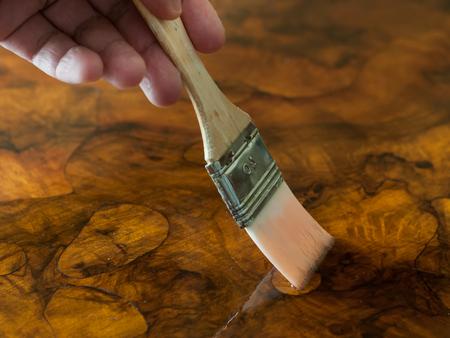 가구 복원. 브러시로 나무 테이블에 기름을 바르는 손. 가로 조성.