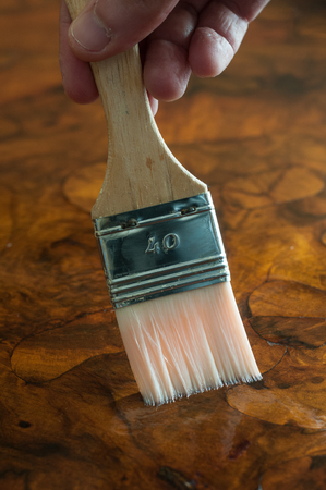 Furniture restoration. Hand oiling a wood table with a brush. Vertical composition. 스톡 콘텐츠