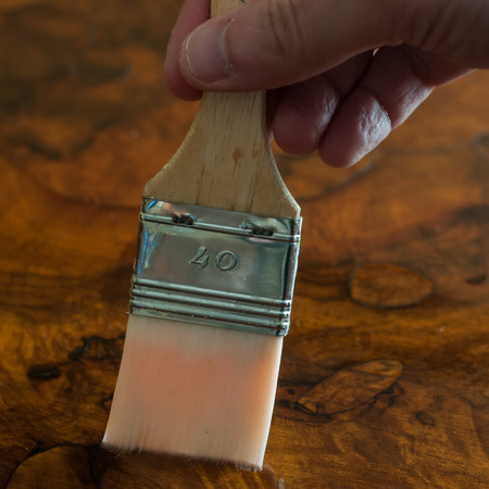 Furniture restoration. Hand oiling a wood table with a brush. Square composition.