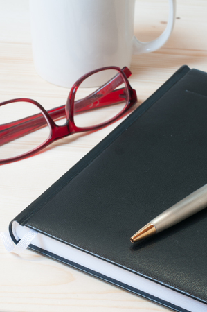 Agenda, pen and glasses  on a wooden table. Office and management concept. Selective focus on the ballpoint pen. Vertical composition. Foto de archivo