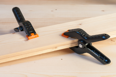 Gluing wood. Detail of two plastic spring clamps joining two pieces of wood. Horizontal composition.