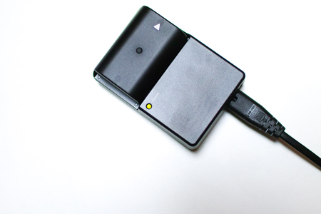 Close-up of a black battery charger isolated on white background.