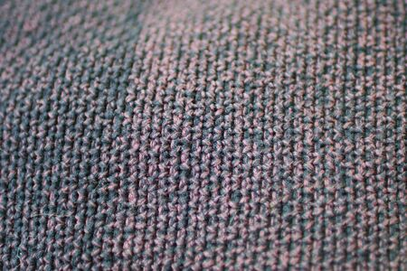 Red-purple and black fabric textured close-up for background. Selective focus on the center of the picture.