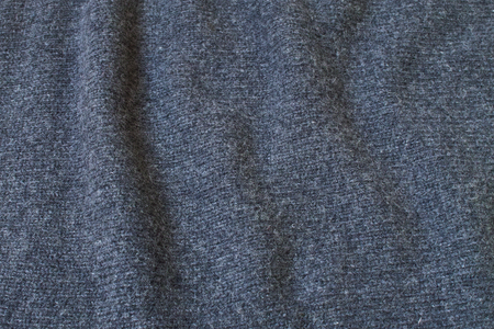 Detail of a dark gray wool sweater. Horizontal composition.