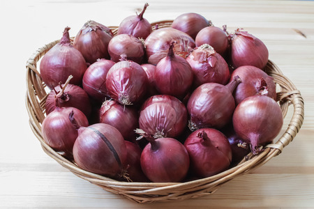 Group of red onions in a wicker basket. Horizontal composition.