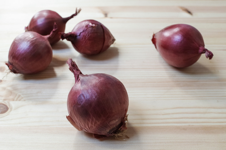 Group of onions on a wooden table. Selective focus on the first onion. Horizontal composition.