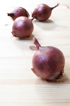 Group of onions on a wooden table. Selective focus on the first onion. Vertical composition.