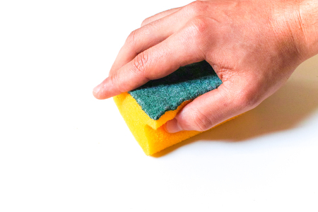 Isolated hand cleaning a white surface with a sponge.