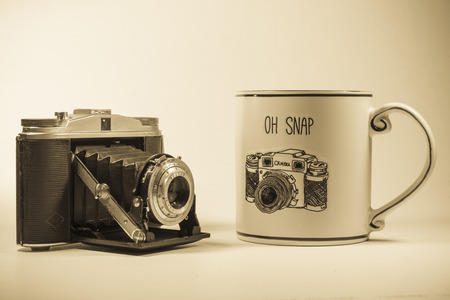 Funny picture of an antique oldfashion camera sitting next to a coffe cup with a funny logo Banco de Imagens
