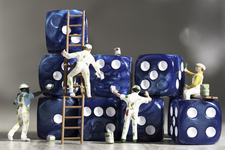 Four Miniature People Painters Painting Blue Dice with White Pips On a Grey Marble Background.
