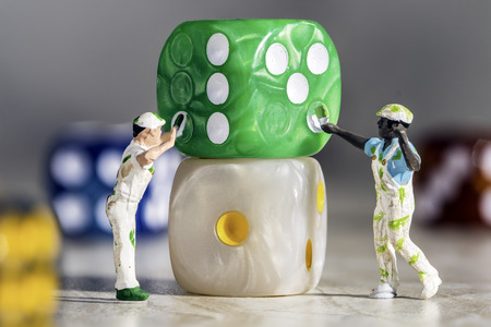 Two Miniature People Painters Painting green Dice with White Pips On a Grey Marble Background. Shows teamwork Stock Photo