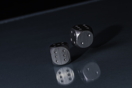 Two Rolling Silver Casino Dice on Black Background with blue bottom