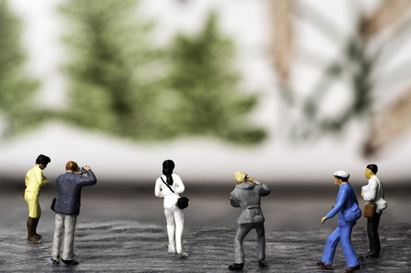 A Group of six Miniature Photographers Figurines taking pictures of a Muriel consisting of trees Standard-Bild