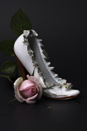 Vintage porcelain high heel white Victorian shoe with wet pink rose on back background.