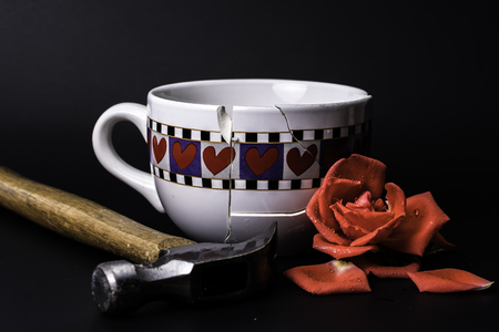 Broken Heart Cup was fixed after it was shattered with hammer and red rose on Black Background Фото со стока