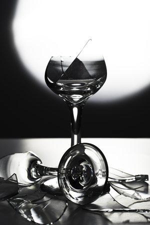Two Broken Champagne Wine Glasses  and shattered glass on Black and White Background