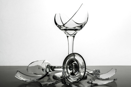 Two Broken Champagne Wine Glasses  with shards of glassand shattered glass on White Background