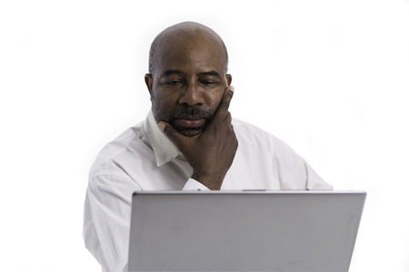 Portrait of thoughtful and pensive African American software expert sitting front of a laptop computer.   Contemplating man working on white background