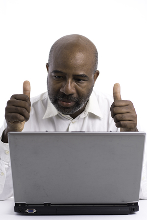 Portrait of a confident African American software expert signaling ok with thumbs up while sitting front of a laptop computer.   Happy man working. Foto de archivo - 124441915