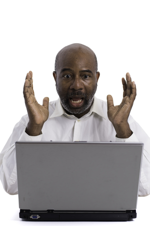 Portrait of astonishedl African American software expert looking surprised while sitting front of a laptop computer.