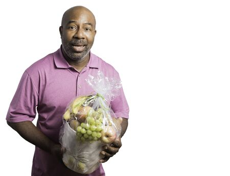African American Man cheerfully holds a fruit basket on white background