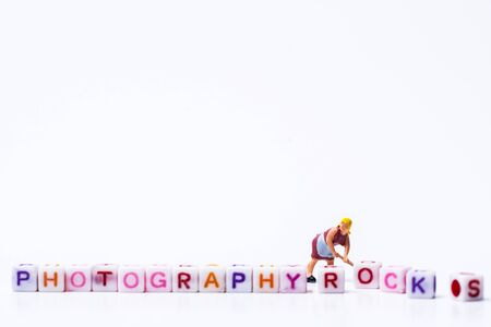Miniature figurine woman fixing adjusting a Group Of Letters forming Words Spelling Stockfoto - 125567503