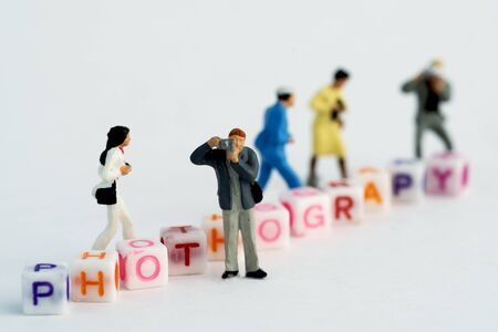 Miniature Photographers taking pictures behind a Group Of Letters forming Word Spelling Stock Photo