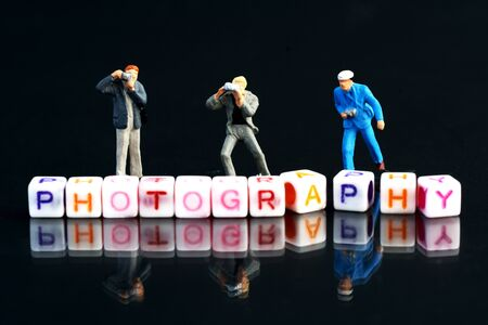 Miniature Photographers taking pictures behind a Group Of Letters forming Word Spelling Stockfoto