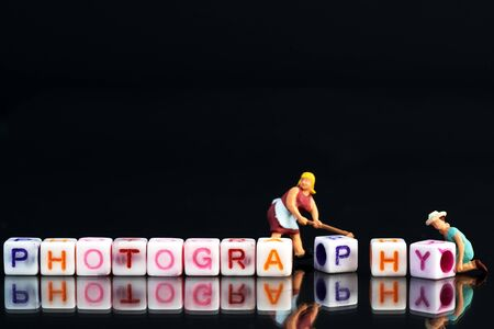 Miniature figurine woman fixing adjusting a Group Of Letters forming Words Spelling Stock Photo