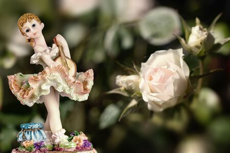 Vintage Girl Figurine wearing petticoat with Guitarre and a white rose on creamy green background. Composition 版權商用圖片