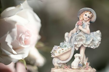 Vintage Girl Figurine wearing petticoat with Bunny  and a white rose on creamy green background. Composition