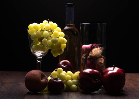 Still life of a glass with grapes, apple, Peach, Plumbs, a bottle and a glass of potpourri sitting on wooden table with black background.  Rembrandt lighting inspired