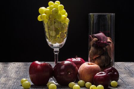 Still life of a glass with grapes, apple, Peach, Plum, and a glass of potpourri sitting on wooden table with black background.  Rembrandt lighting inspired Banque d'images