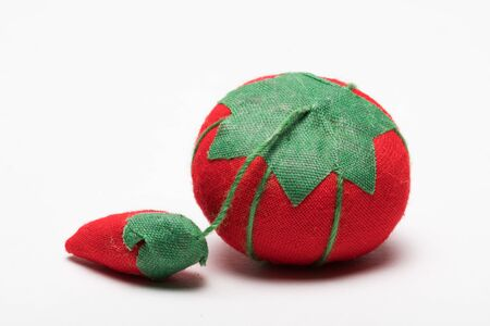 Pin Cushion without pins made out of red and green fabric isolated on white background