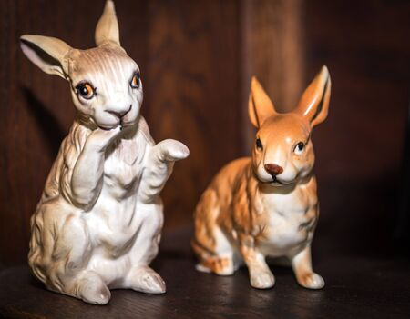 Two porcelain vintage bunny figurines with wooden background. Easter Concept Stock Photo