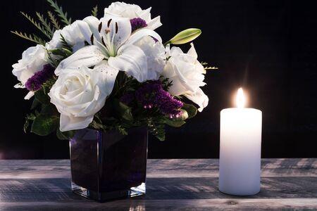 Ramo de flores blancas en un jarrón púrpura, vela blanca sobre tablas de madera. Decoración del hogar vintage en tonos oscuros. Tarjeta de condolencia.