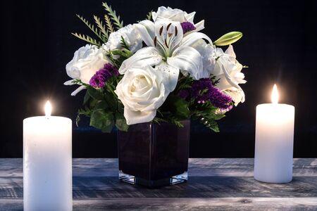 Strauß weißer Blumen in lila Vase, weiße Kerze auf Holzbrettern. Vintage Wohnkultur dunkle Töne. Kondolenzkarte.