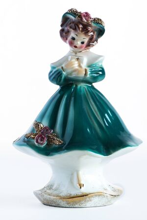 Porcelain Vintage  girl figurine with prayer book in blue dress and brown hair on white background.