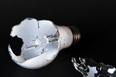 Broken lightbulb isolated on black background