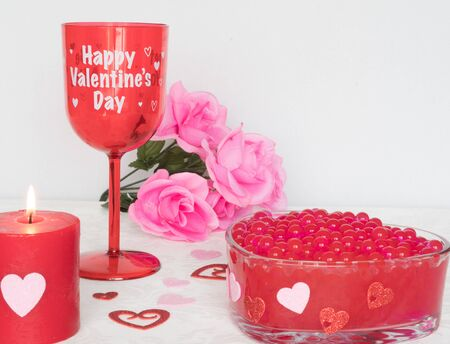 Valentines Day still life with red glass, candle, and pink roses. Romantic Concept on white soft background.