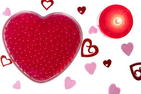 Valentine Heart with burning candle and red pearls and small hearts. Mothers Day with Top View. Reklamní fotografie