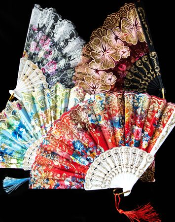 Flamenco hand fans with colorful pattern isolated on black  background. Spanish or Chinese influence