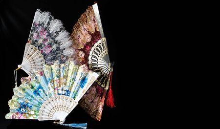 Flamenco hand fans with colorful pattern isolated on black  background. Spanish or Chinese influence with copy space