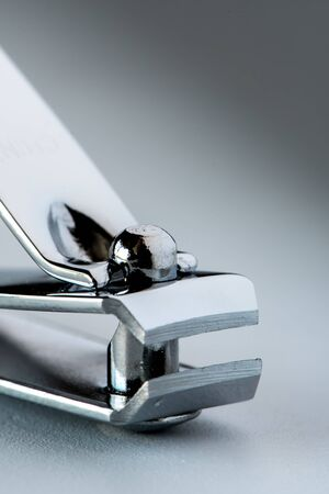 front view of nail clipper isolated on grey  background. Close up with blurry end.