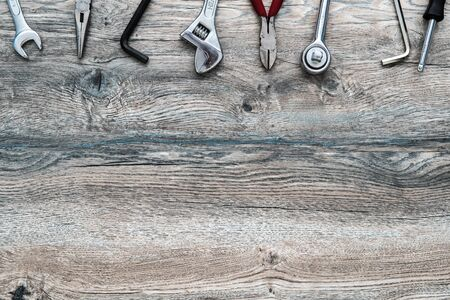 Tools, adjustable wrench, socket wrench, pliers on wood background, top view, flat lay with copy space